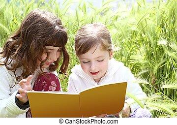 two little sister girls reading book spikes garden