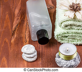 Towel, bottle of oil and a candle on the stone