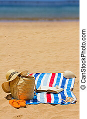 towel and sunbathing accessories on beach by sea