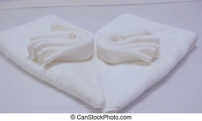 Towel swan in a hotel room or cruise cabin on the bed.