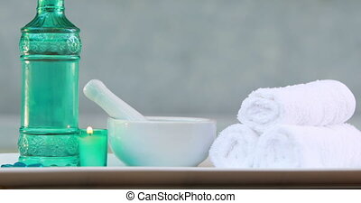 Towels and glass bottle with candle and mortar and pestle at...