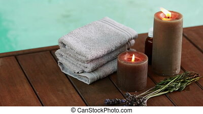 Towels candles and dried lavender by the pool at the spa