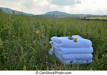 Towels on meadow with yellow flowers
