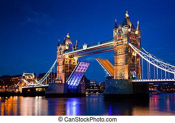 Tower Bridge in London, the UK at night. The bridge is opening