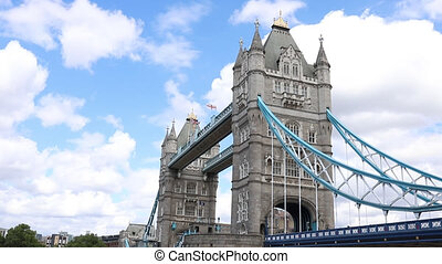 Landscape FHD Video of Tower Bridge (inaugurated in 1894) during a sunny day and with a cloudy blue sky as background