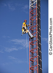 Tower climber ascending the guyed tower - seen against blue...