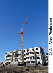 Tower crane and building on the sky background