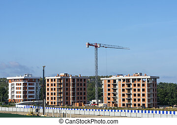 Tower crane at a construction site. Construction of multi-apartment high-rise buildings. New building