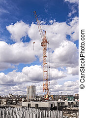 Tower crane near the house under construction on the background of a cloudy sky