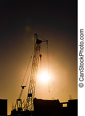 Tower crane on a construction site at sunset