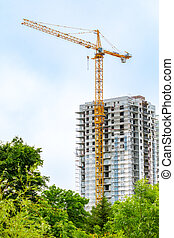 Tower crane on the background of a high-rise building under construction.