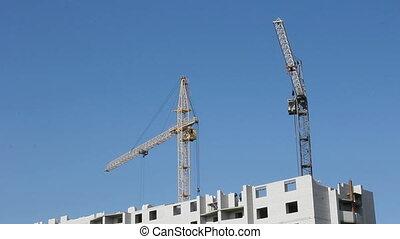 Tower cranes against blue sky