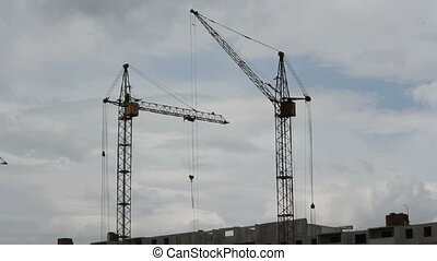 Tower cranes against blue sky, with