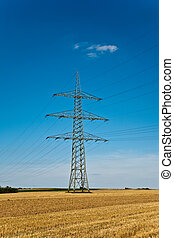 tower for electricity in beautiful landscape with golden fields