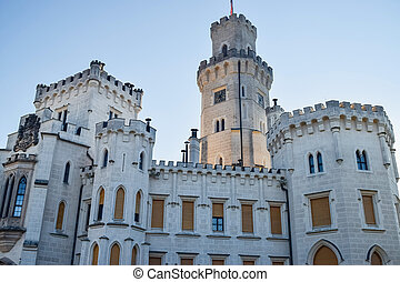 Tower of ancient European castle with clock and windows and battlements on roof for defense