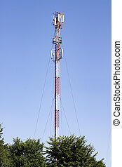 Tower of communication against the sky and green trees