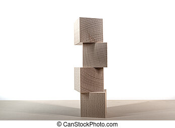 tower of four wooden blocks on table against white background