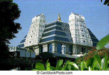 View of tower of ISKCON Temple behind foliage at Bengaluru in Karnataka, India, Asia