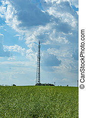 Tower of mobile communication against the blue sky with white clouds