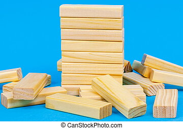 Tower of wooden blocks on blue