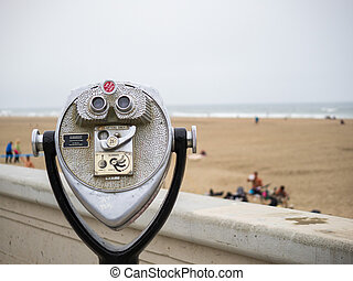 Tower viewer telescope and binoculars looking off to ocean and beach on overcast day with storm coming