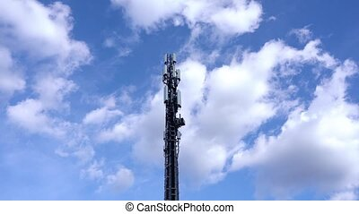 Cell tower with antennas transmits internet radio and TV signals to homes studios under blue sky with white clouds low angle shot