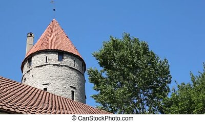 tower with red roof tiled and tree nearby against sky