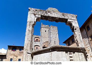 towers and medieval well on Piazza della Cisterna in San Gimignano in tuscany in italy