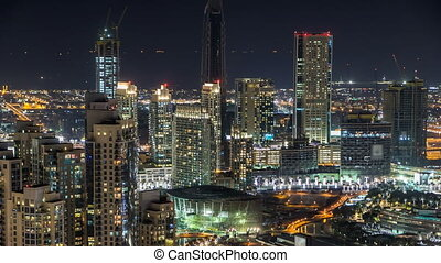 Towers and park near man-made lake timelapse in Dubai downtown, United Arab Emirates.