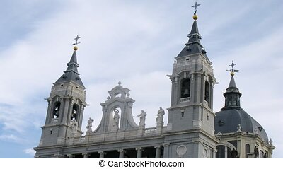 Towers of Almudena Cathedral stands against clouds, time lapse