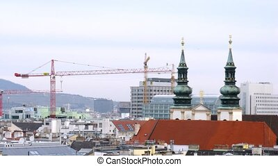 Towers of Jesuit church stand near cranes against roofs of houses