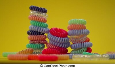 Towers of spiral elastic hair bands on a yellow background