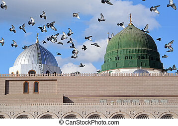 Prophet Muhammed holy mosque and pigeons flying in the sky in Medina, KSA