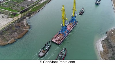 Towing cranes for containers. Large container ship pulled by...