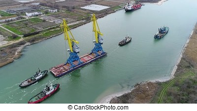 Towing cranes for containers. Large container ship pulled by tugboats. Top down aerial view. Container Cargo freight ship with working crane bridge in shipyard at dusk for Logistic Import Export background