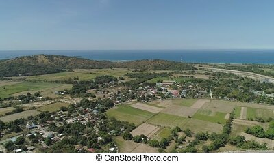 Town and farm fields near the sea. - Town near the sea with...