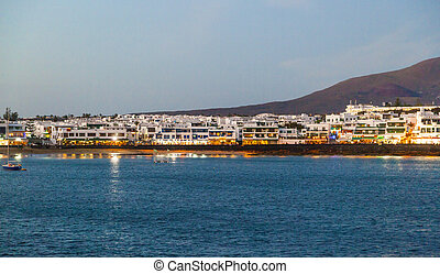 town and harbor of Playa Blanca from seaside in the evening