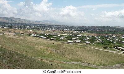 Town at Bottom of Mountainous Hill - Handheld, panning,...