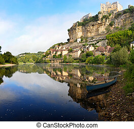 The beautiful village of Beynac-et-Cazenac with its characteristic Chateau de Beynac castle built upon the cliffs alongside Dordogne river in the early morning light with reflection in the water and a kayak in the foreground in the Perigord region in France.