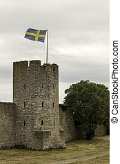 Town Wall in Visby, Gotland with the Swedish flag.