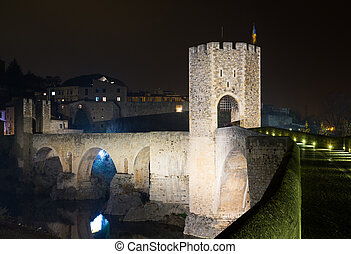 town with gate on bridge in night. Besalu, Catalonia