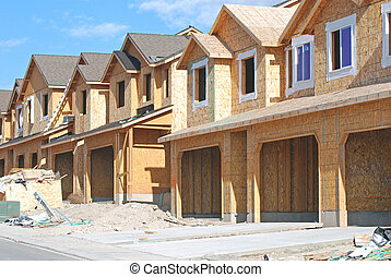 Rows of unfinished townhouses under construction.