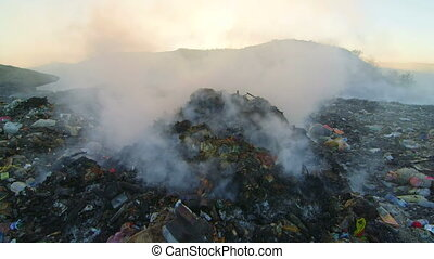 Toxic smoke from burning dump rises into the air tilt up