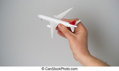 Toy airplane in the hand simulates a flight - White toy...
