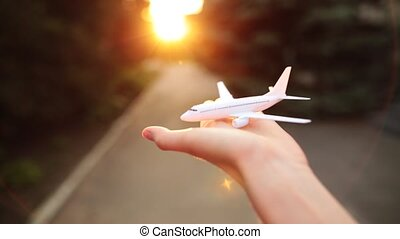 Toy airplane in the palm of a girl on a sunset background.