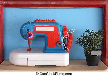 Toy and vintage sewing machine on blue background with pot...