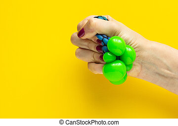 Toy anti-stress in a female hand on a yellow background