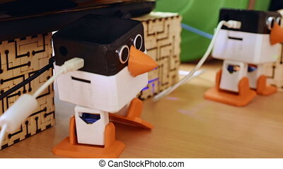 Toy automatic robots are dancing on the table. Robotics and...