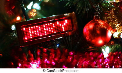 toy ball and behind him LED display with running line MERRY CHRISTMAS on New Year tree