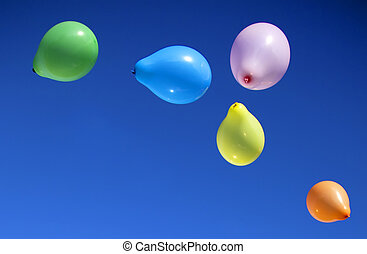 Toy balloons fly in the sky.